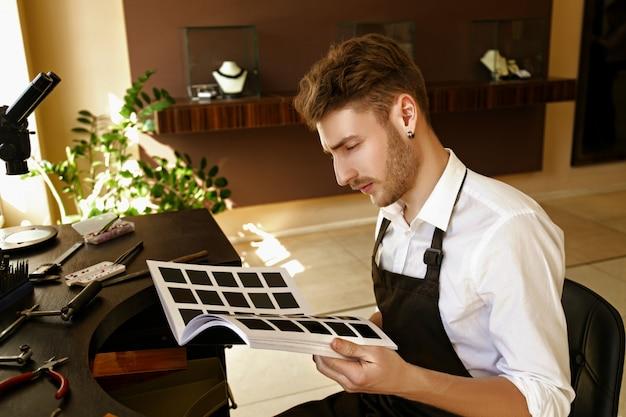 装飾品のカタログを閲覧する男性の宝石商
