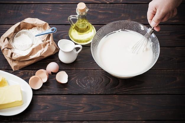 Тесто и продукты для его приготовления на темном деревянном столе