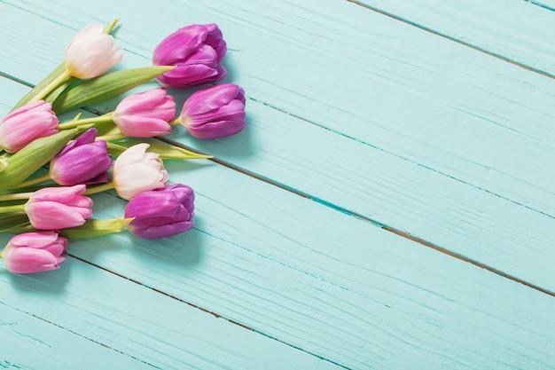 青いミントの木製テーブルの春の花