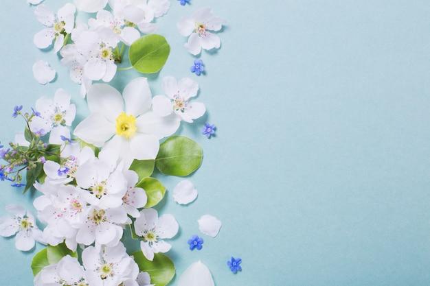 緑の紙の背景に白い水仙と桜の花