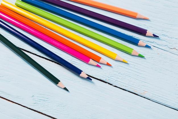 Разноцветные карандаши на синем деревянном столе
