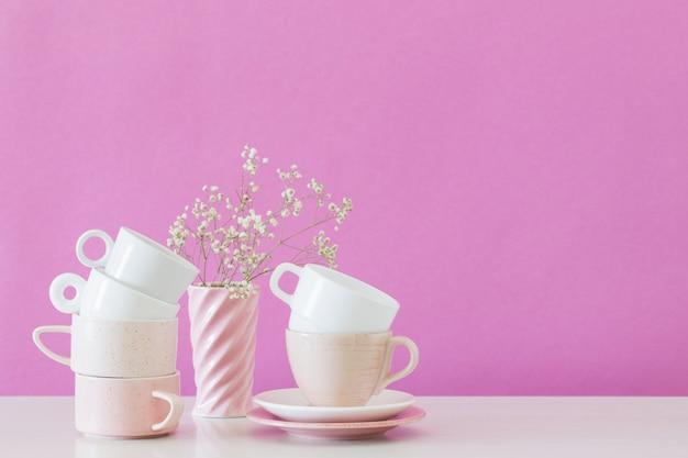 Современные чашки на белом столе на фоне розовой стены