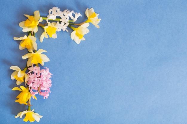 青い紙の背景に春の花