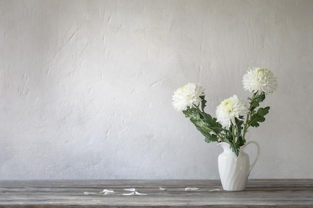 Белая хризантема в кувшине на фоне старой стены