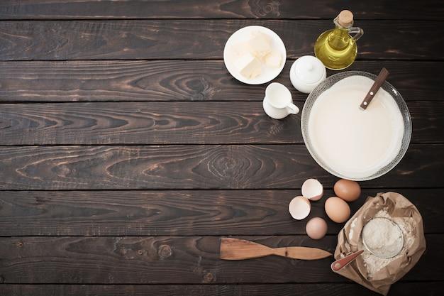 Тесто и продукты для его приготовления на темном деревянном фоне