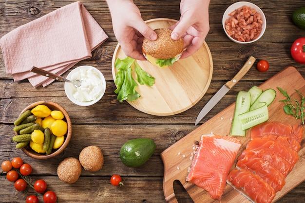 古い木製の背景に手で健康的なハンバーガー