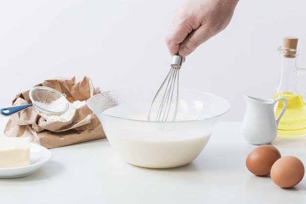Тесто в стеклянной тарелке и продукты для его приготовления на белой поверхности