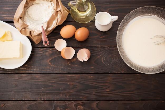 Тесто и продукты для его приготовления на темной деревянной поверхности