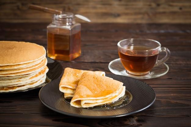 古い木製の表面に蜂蜜とお茶のカップのパンケーキ