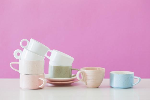 Сложенные чашки на белом столе