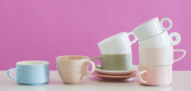 背景ピンクの壁に白いテーブルにモダンなカップ
