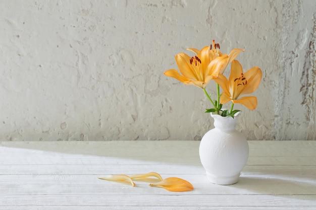 白い背景に白い花瓶のユリ
