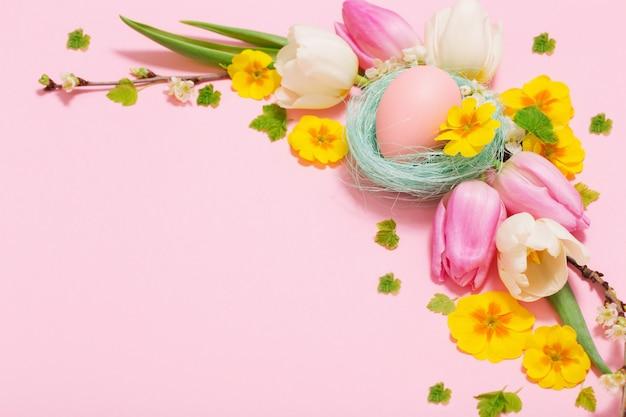 Пасхальные яйца и весенние цветы на розовом фоне