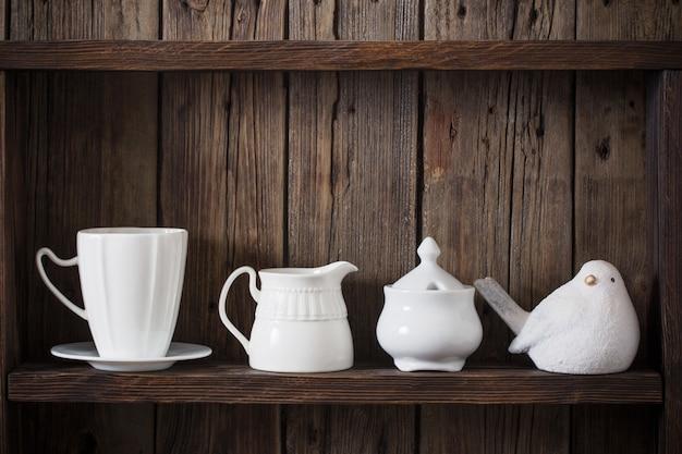 Белая кухонная посуда на старом темном деревянном фоне