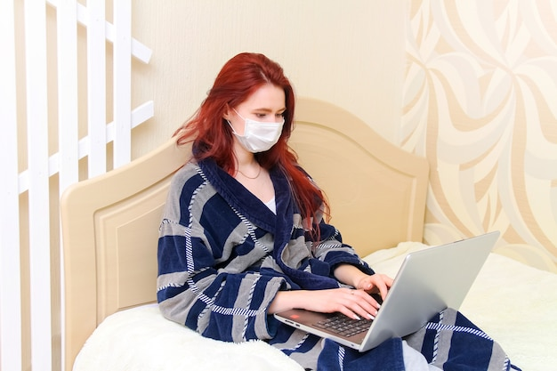 Молодая девушка сидит на кровати в медицинской маске, она болеет и работает дома в постели с ноутбуком