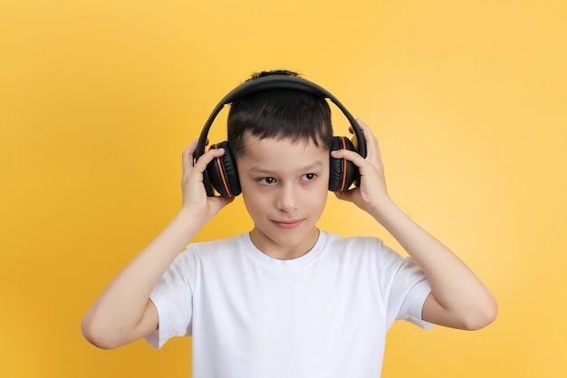 Мальчик с большими черными наушниками слушает музыку на желтом фоне
