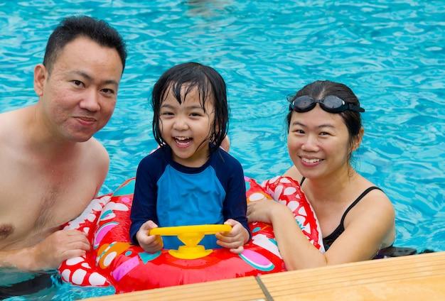 幸せな家族がプールで遊んで