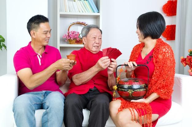 中国の新年の親にギフトバスケットと赤いパケットを提示するアジアの子供