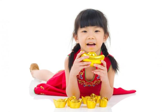 伝統的な中国のチャイナドレスの挨拶、スタジオで横になっているゴールドインゴットを保持