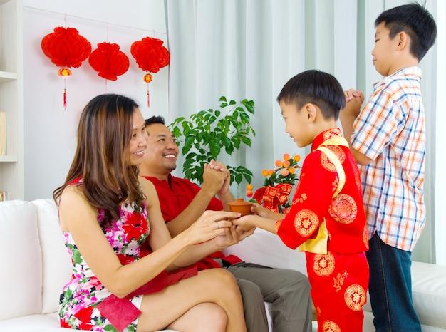 アジアの少年が中国の新年の間に彼の母親にお茶を差し出す