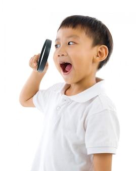 中国人の少年が白い背景で隔離の虫眼鏡を通してカメラをのぞきます