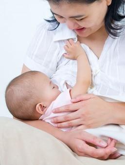 アジアの母親が彼女の女の赤ちゃんを母乳で育てる