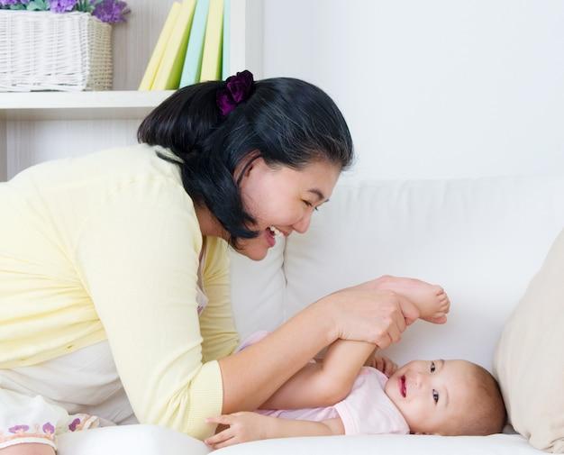 彼女の女の赤ちゃんを母乳で育てるアジアの母