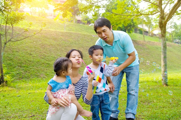 アジアの家族が屋外のシャボン玉を吹く
