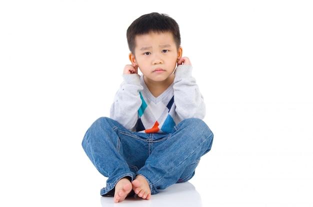 Милый мальчик чувствует себя виноватым с прикосновением руки к его уху