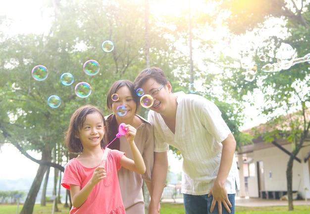夏の間に屋外の公園で一緒に泡を遊んでうれしそうな幸せなアジア家族の肖像画