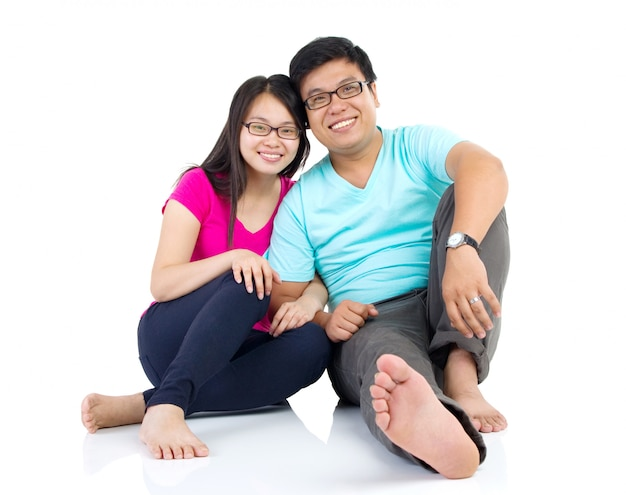 Счастливая молодая пара, сидя на полу