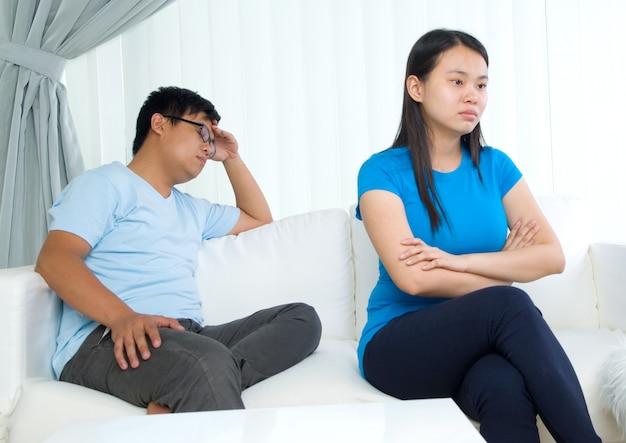 リビングルームで引数を持っているアジアの若いカップル