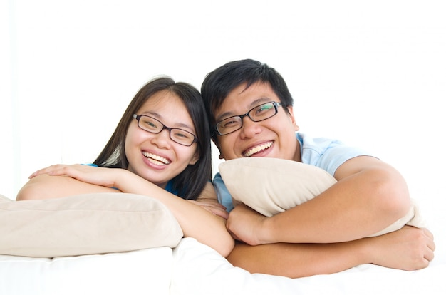 Сладкая молодая пара, сидя на диване