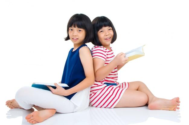 床に座って読んでいるアジアの女の子。白い背景に分離されました。