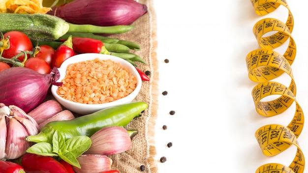 Красная чечевица и сырые овощи, изолированные на белом крупным планом
