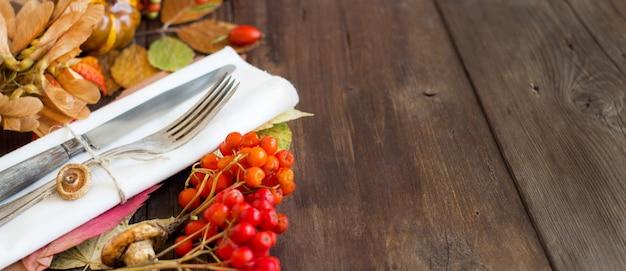 茶色の木製のテーブルに秋の素朴なテーブルセッティングをコピースペースでクローズアップ