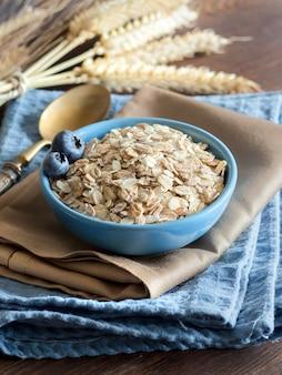 Сырой овсяных хлопьев в миску на салфетке на деревянном столе крупным планом