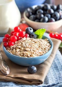 Сырой овсяных хлопьев в миску с ягодами и молоко на салфетке на деревянном столе крупным планом