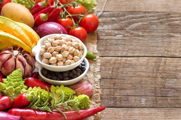 コピースペース付きの木製テーブルで野菜をボウルにひよこ豆をクローズアップ