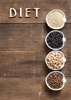 Зерновые и бобовые в мисках с текстом диета на деревянном столе с бумажной копией пространства вид сверху
