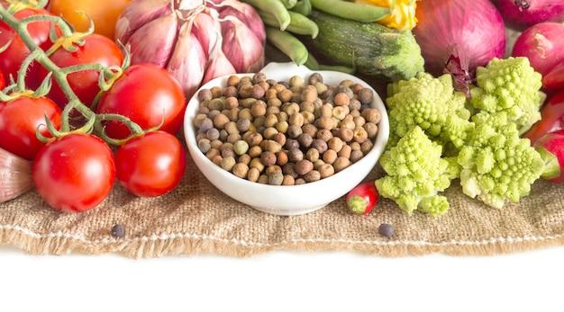 生の乾燥有機ロベヤ豆と白で隔離される野菜をクローズアップ