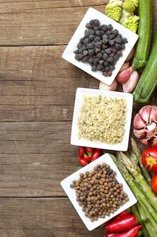 ロベジャ、大麻の種子、ボウルに黒ひよこ豆と野菜コピースペース付きの木製テーブルトップビューで野菜