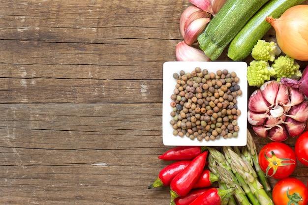 コピースペースを持つ木製テーブルトップビューで野菜をボウルに生の有機ロベヤ豆