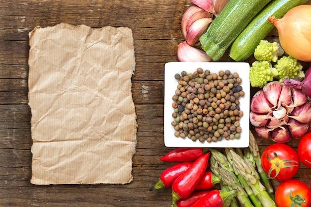 ペーパーコピースペースを持つ木製テーブルトップビューで野菜をボウルに生の有機ロベヤ豆