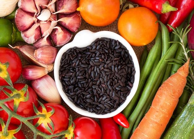 Черный органический рис в миску между сырыми овощами