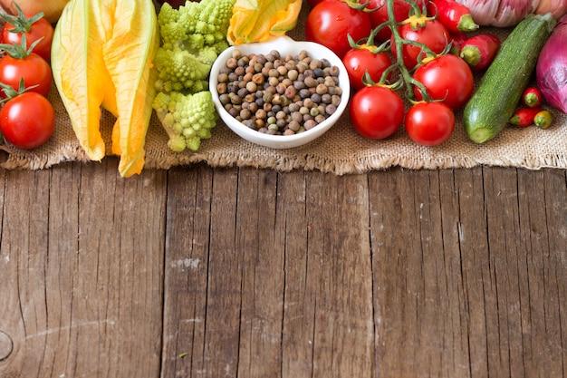 木製のテーブルで生野菜をボウルに生の有機ロベハ豆をコピースペースでクローズアップ