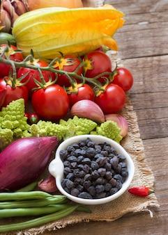 木製のテーブルで生野菜をボウルに黒いひよこ豆をコピースペースでクローズアップ