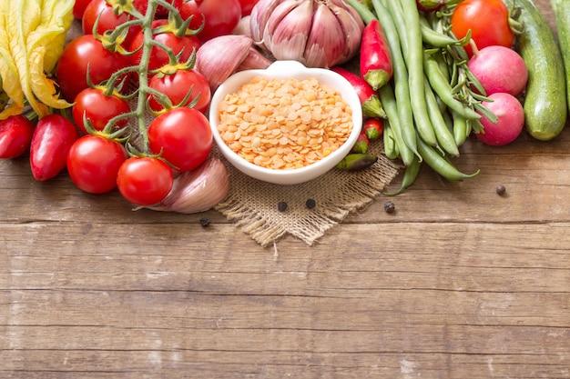 ボウルに生の乾燥赤レンズ豆と木製のテーブルで野菜をコピースペースでクローズアップ