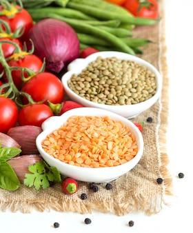 ボウルと黄麻布の野菜の生の乾燥した緑と赤レンズ豆を白の分離をクローズアップ