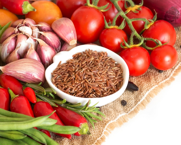 ボウルに生の乾燥赤米と黄麻布の野菜を白のクローズアップを分離します。